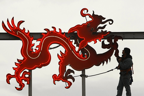 A worker checks the light on a symbol of the Red Dragon Chinese market in the outskirts of Bucharest