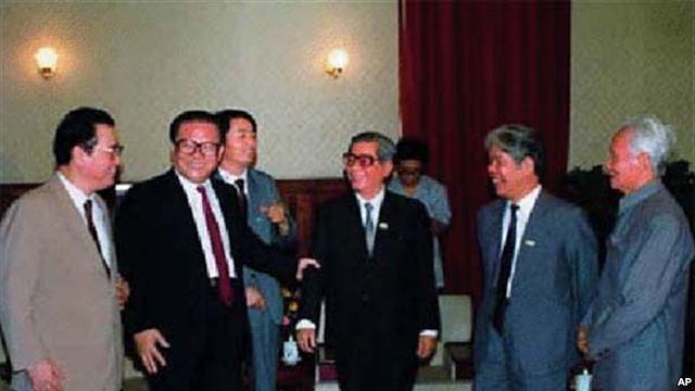 Đứng giữa là Giang Trạch Dân và Lý Bằng. Ông Giang cầm cánh tay Nguyễn Văn Linh. Bên trái là Đỗ Mười và Phạm Văn Đồng (chắp tay)