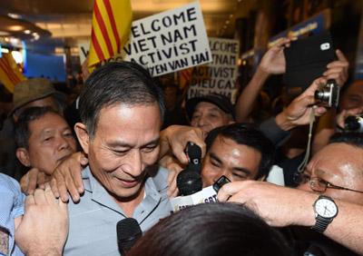 Nhà báo tự do Nguyễn Văn Hải tức blogger Điếu Cày bị đưa thẳng từ nhà tù ở Nghệ An sang Mỹ, được đồng hương chào mừng ở phi trường Los Angeles buổi tối 21/10/2014. (Hình: ROBYN BECK/AFP/Getty Images)