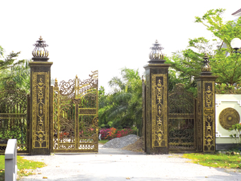 """Cổng chính đi vào dinh thự và """"dự án gia đình"""" của ông Trần Văn Truyền màu sắc như sơn son thếp vàng."""