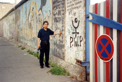 Tác giả đứng bên một đoạn Bức Tường Berlin hồi năm 2000.  (Hình: Huy Phương cung cấp)