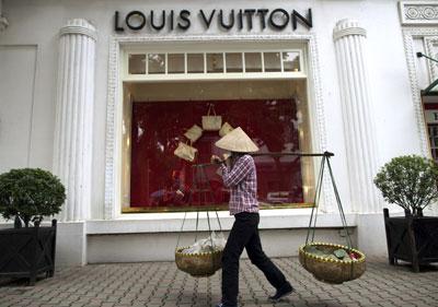 Sự chênh lệch giàu nghèo thể hiện rõ trên đường phố Hà Nội  như trong hình một người buôn gánh bán bưng đi ngang qua  cửa hàng thời trang nổi tiếng thế giới Louis Vuitton. (Hình: Getty Images)