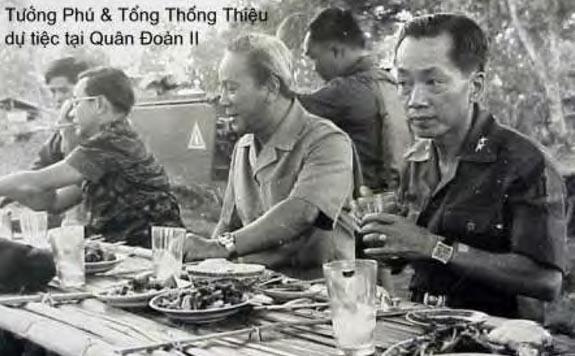 """Bữa tiệc mừng xuân 1975 cũng là """"bữa tiệc ly cuối cùng"""" giữa Tướng Thiệu, Tướng Khang, Tướng Phú và anh em chiến sĩ Trung đoàn 44/ Sư đoàn 23 BB tại vùng hỏa tuyến Pleiku.  Chiếc bàn ăn đơn sơ, thức ăn đơn sơ, với những khuôn mặt đăm chiêu là điềm báo cho tương lai chua xót của những người bảo vệ đất nước không thành công."""